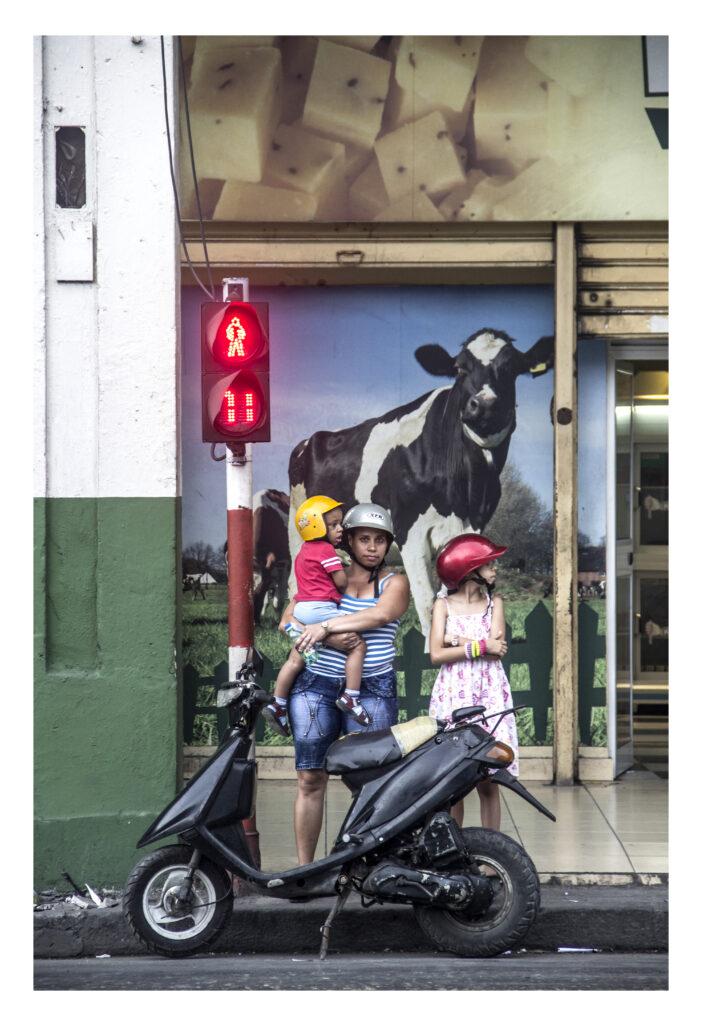 Una mujer con dos hijas, las tres con cascos de moto.