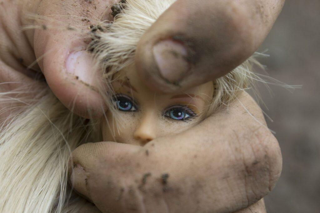 La cabeza de una muñeca rubia de ojos azules apretada por una mano de hombre sucia.