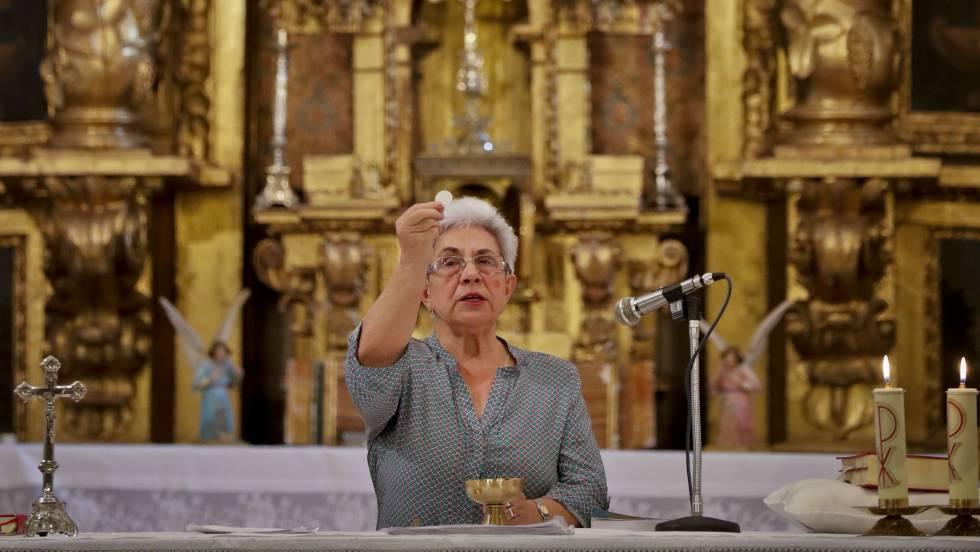 Mujer de avanzada edad consagra la ostia en el altar de un templo católico.