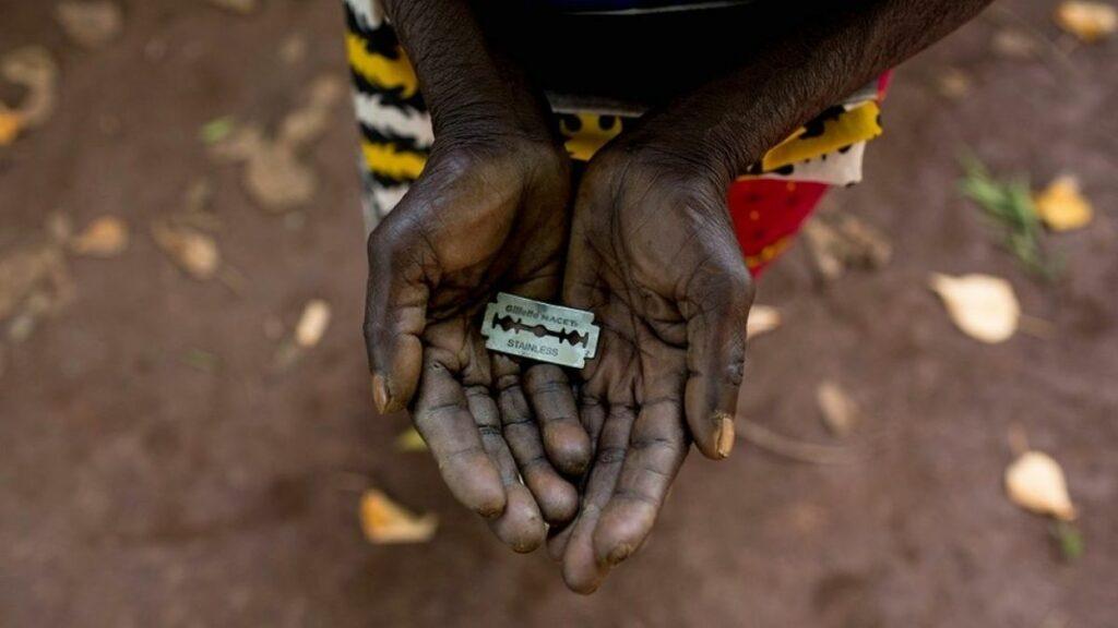 Una cuchilla de afeitar en las manos de una mujer negra y anciana.