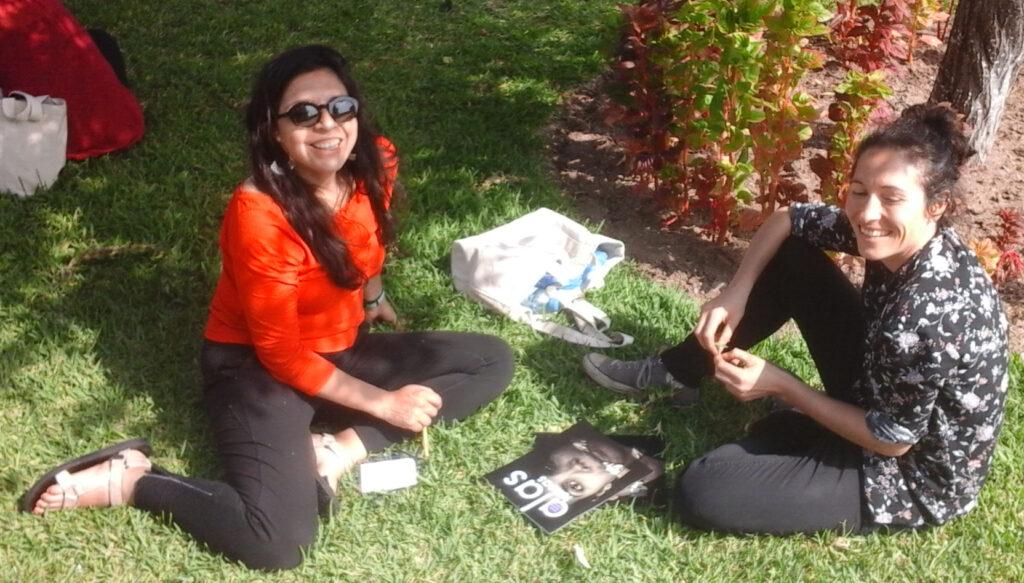 Dos muchachas sentadas sobre el césped junto a una revista Alas Tensas.