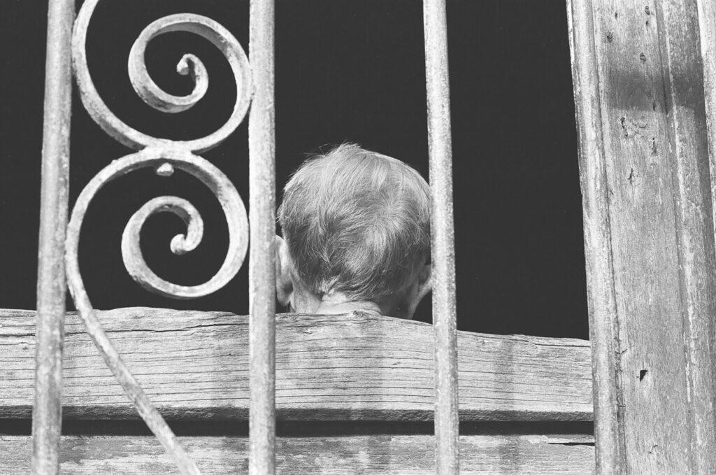 Persona anciana de espadas en ventana antigua.