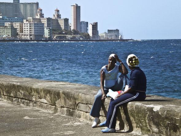 Dos mujeres negras de avanzada edad conversan en el malecón de La Habana.