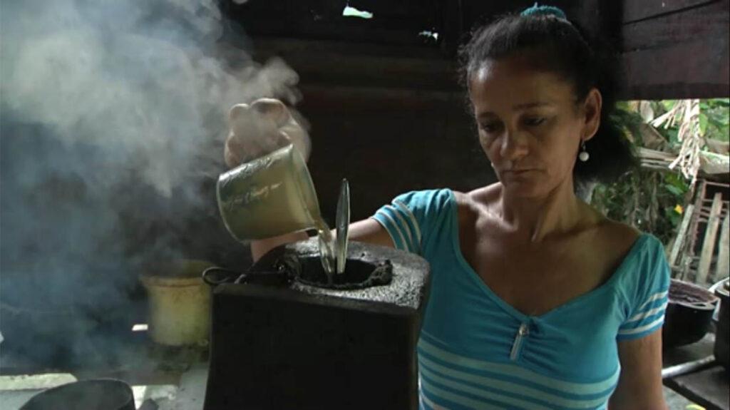 Mujer campesina prepara café en condiciones muy rústicas.