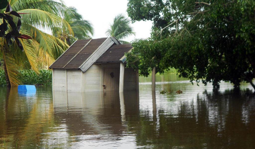 Pequeña casa de madera en medio de una inundación.