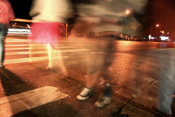 Silueta transparentada de una mujer con falda roja cruzando la calle.