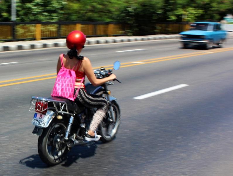 Mujer conduce una motocicleta llevando un casco rojo y una jaba rosada a la espalda.