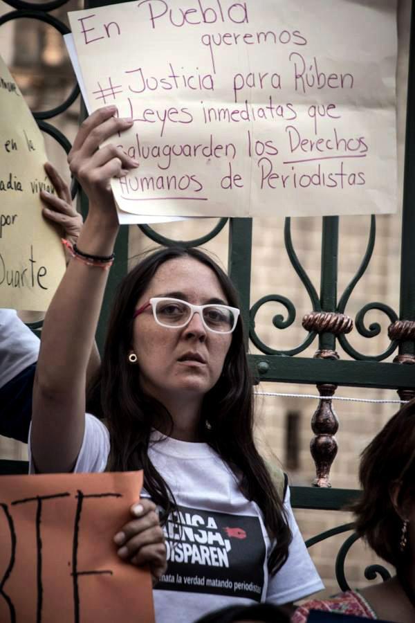 La periodista mexicana Aranzazú Ayala Martínez alzando un cartel con reclamaciones de derechos humanos.