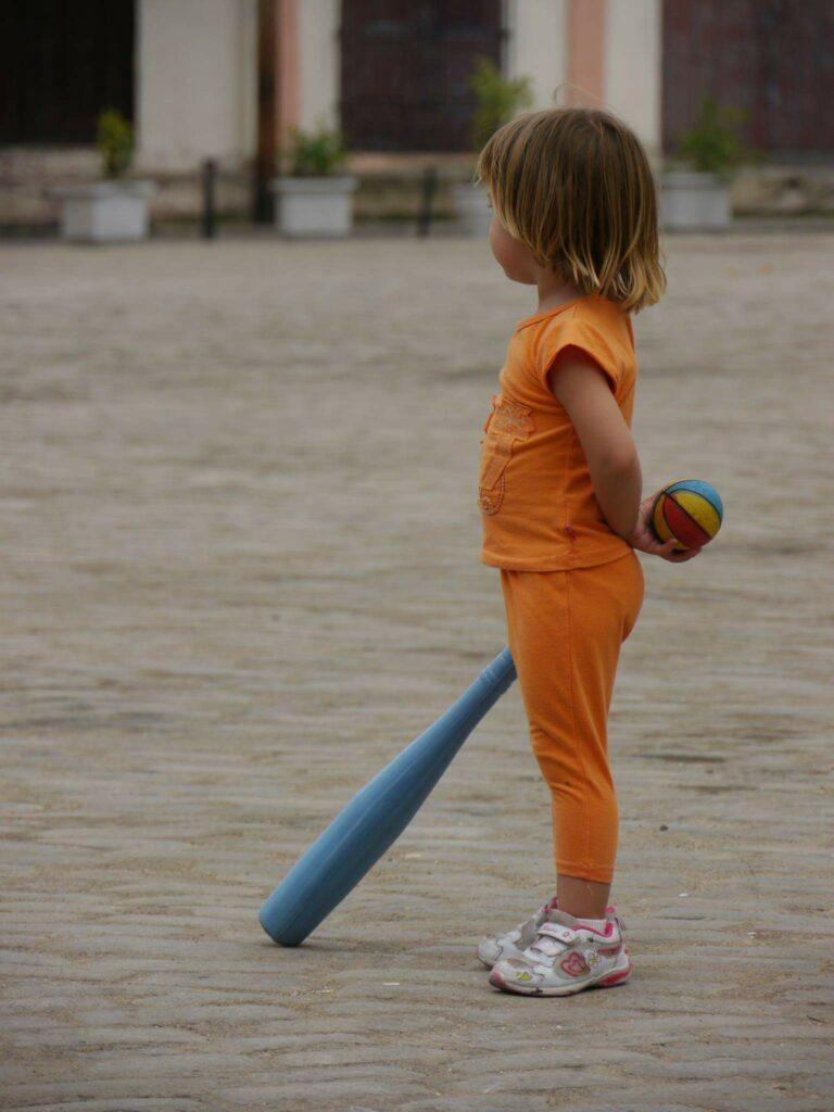 Niña con un bate de béisbol azul y una pelota de colores.