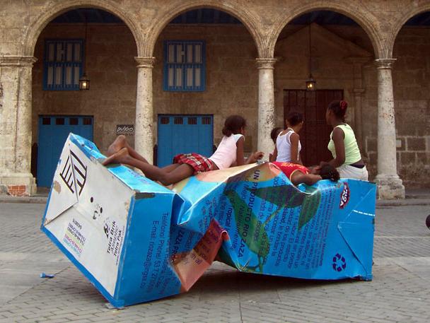 Niñas acostadas sobre una escultura que es una caja de jugo gigante.